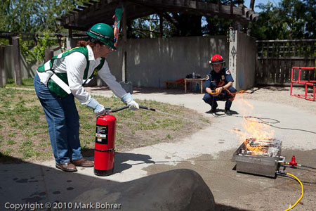 Saratoga CERT volunteer Madeleine extinguishing the fire while Rob Hecocks watches during West Valley College / Saratoga CERT disaster preparedness exercise