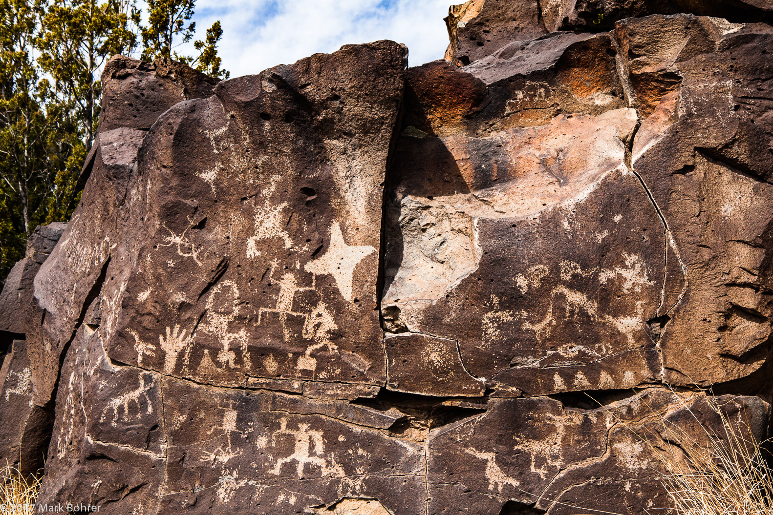 Toothy open-mouthed war god at center right - star kachina at center left - La Cieneguilla Petroglyph Site